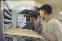 Laurent Le Gaudu n'hésite pas à conseiller un jeune apprenti dans une boulangerie.