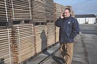 Alban Petiteaux, dans le parc de 10 hectares où son stockées les palettes de bois, téléphone à ses commerciaux.