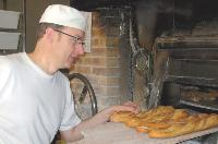 A la Boulangerie d'Honoré, Patrice Guillois enfourne ses baguettes sous les yeux de ses clients.