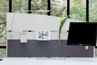 Si Les cloisons pour séparer les postes de travail sont de plus en plus équipées. Ce modèle Triplex du fabricant Majencia dispose d'un rail supportant des accessoires de rangement, des lampes et un écran d'ordinateur.
