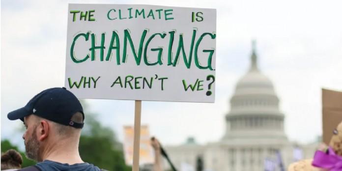 Manifestation en 2017 à Washington (États-Unis). On peut lire sur la pancarte : ' Le climat change. Pourquoi pas nous ? ' shutterstock